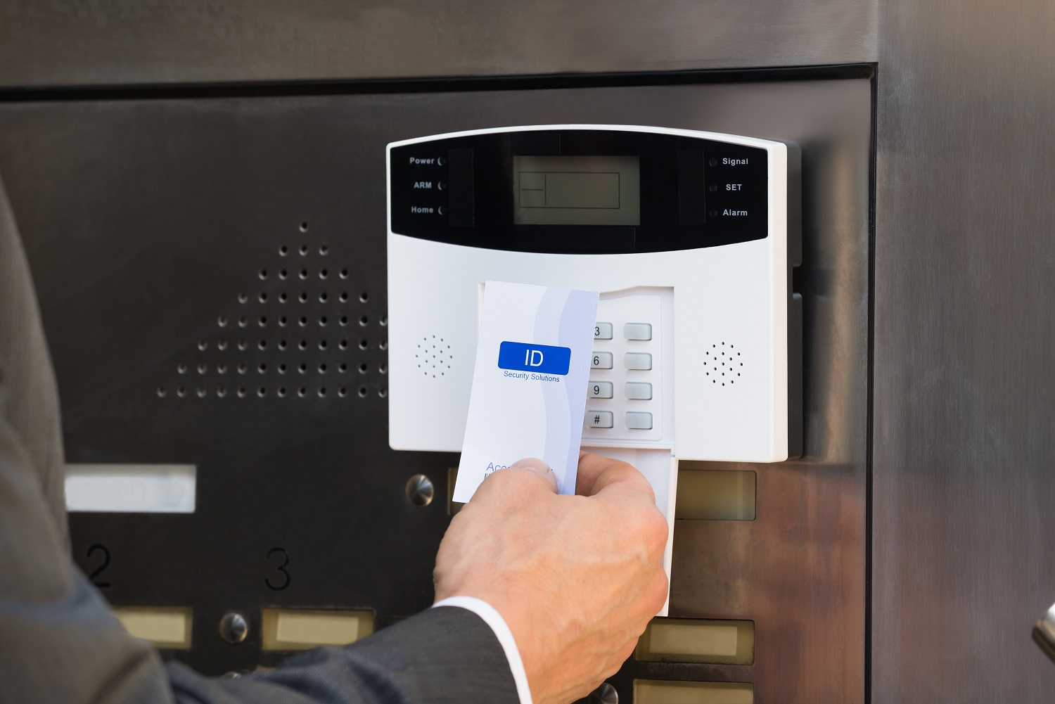 Close-up Of Businessperson Hands Inserting Keycard In Security System To Unlock Door